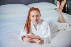 Peignoir de port de belle femme et à l'aide du comprimé numérique tout en détendant sur le lit photos libres de droits