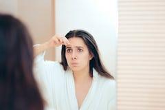 Peignoir de port de femme plumant ses sourcils après douche images stock