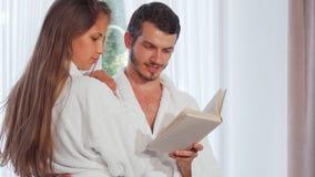 Peignoirs de port de couples heureux lisant un livre ensemble banque de vidéos