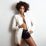 Peinado afro joven de la mujer negra possing cerca de una pared blanca Imagen de archivo libre de regalías