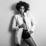 Peinado afro joven de la mujer negra possing cerca de una pared blanca Imagen de archivo
