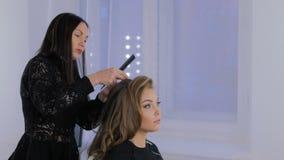 Peinado del acabamiento del peluquero para el cliente almacen de metraje de vídeo