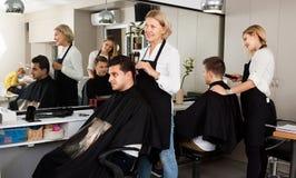 Peinado que hace femenino para la porción rubia del peluquero del hombre adulto Foto de archivo