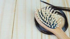 peine con el pelo de la pérdida en de madera Imágenes de archivo libres de regalías