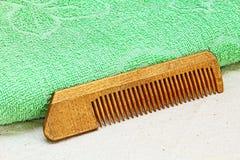 Peine de madera del pelo y toalla verde en el paño blanco Foto de archivo