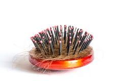 Peine el pelo con los penachos, paquete del pelo, porciones de pelo en el cierre del cepillo para el pelo para arriba en un blanc Foto de archivo libre de regalías