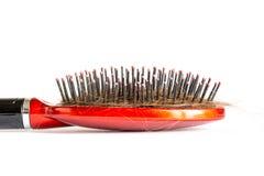 Peine el pelo con los penachos, paquete del pelo, porciones de pelo en el cierre del cepillo para el pelo para arriba en un blanc Fotografía de archivo