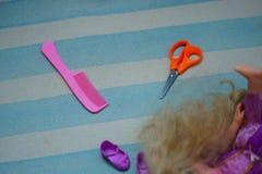 Peine, pelo, muñeca y tijeras fotografía de archivo
