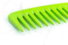 Peine verde con el pelo Imagenes de archivo