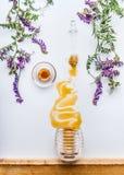 Peine y cazo de la miel con las manchas de la miel del tarro con las flores salvajes en el fondo blanco Fotos de archivo libres de regalías