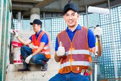Peintre asiatique avec la brosse et peinture sur le chantier de construction Photographie stock libre de droits