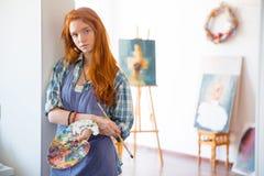 Peintre atractive réfléchi de jeune femme tenant la palette et la brosse d'art Photographie stock libre de droits
