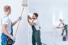 Peintre avec des gants peignant le mur Photographie stock libre de droits