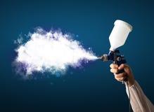 Peintre avec l'arme à feu d'aerographe et la fumée magique blanche Photo libre de droits