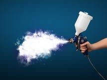 Peintre avec l'arme à feu d'aerographe et la fumée magique blanche Photographie stock