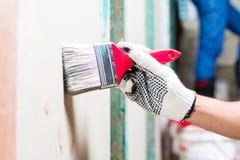 Peintre avec la brosse et peinture sur le chantier de construction photographie stock libre de droits
