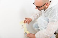 Peintre collant la bande près de la prise photographie stock libre de droits