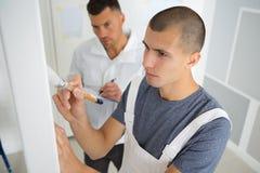 Peintre d'apprenti travaillant sous la surveillance image libre de droits