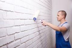 Peintre de jeune homme dans le mur de briques uniforme de peinture avec le petit pain de peinture Photo libre de droits