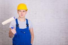 Peintre de jeune homme dans les vêtements de travail avec le pinceau de rouleau au-dessus du blanc Photographie stock