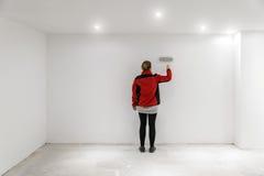 Peintre féminin avec le rouleau de peinture devant le mur comme calibre Photo libre de droits
