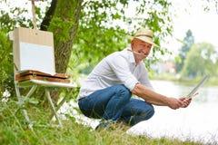 Peintre heureux s'asseyant avec la photo en nature Photographie stock libre de droits