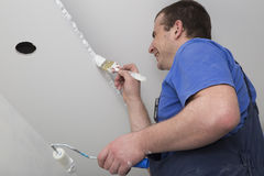 Peintre peignant un plafond de maison avec la brosse et le rouleau images libres de droits