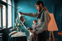 Peintre regardant la peinture de toile contre le poseur Images stock