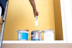 Peintre sur une échelle plongeant sa brosse dans la boîte de peinture Photographie stock