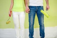 Peintres de couples avec des rouleaux de peinture Images stock