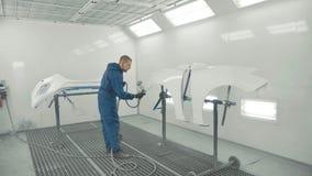 Peinture blanche de pulvérisation de peintre automatique sur l'amortisseur de pièce de rechange de voiture dans la cabine spécial Image libre de droits