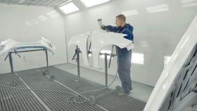 Peinture blanche de pulvérisation de peintre automatique sur l'amortisseur de pièce de rechange de voiture dans la cabine spécial Photo libre de droits