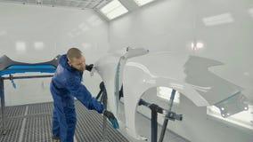 Peinture blanche de pulvérisation de peintre automatique sur l'amortisseur de pièce de rechange de voiture dans la cabine spécial Images libres de droits