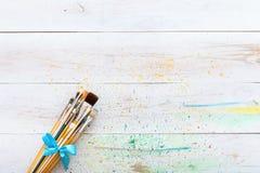 Peinture brosse de lecture sur la table souillée peinte en bois blanche avec éclabousse, le fond artistique de toile, l'espace cr images stock