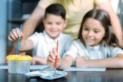 Peinture créative d'enfant de mêmes parents avec des aquarelles Photos stock
