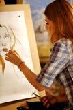 Peinture d'artiste sur le chevalet dans le studio La fille peint le portrait de la femme avec la brosse photo stock