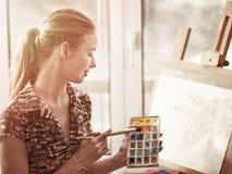 Peinture d'artiste sur le chevalet dans le studio Peintures de fille avec la brosse photo libre de droits