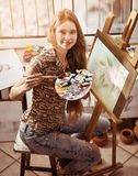Peinture d'artiste sur le chevalet dans le studio Peintures de fille avec la brosse images libres de droits