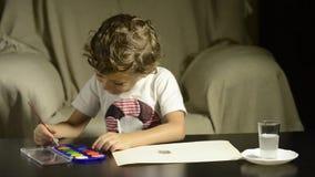 Peinture d'enfant avec des aquarelles sur le papier banque de vidéos