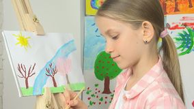 Peinture d'enfant sur le chevalet, enfant d'école dans la classe d'atelier, métier travaillant d'art de fille banque de vidéos