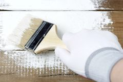 Peinture d'une surface en bois avec la peinture blanche, une main enfilée de gants tenant un pinceau photo libre de droits