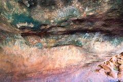 Peinture de caverne indigène à l'intérieur du mutitjulu de caverne ou de kulpi de famille à la roche d'Ayers dans l'intérieur Aus photos stock
