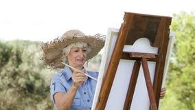 Peinture de dame âgée en parc banque de vidéos