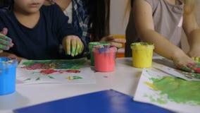 Peinture de doigt ethnique multi de petites filles à la classe banque de vidéos