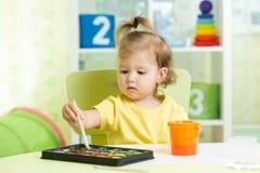 Peinture de fille d'enfant avec les aquarelles à la maison ou la crèche préscolaire Photographie stock
