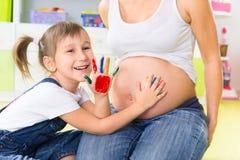 Peinture de fille de Llittle sur le ventre enceinte Image stock