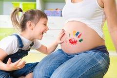 Peinture de fille de Llittle sur le ventre enceinte Images stock