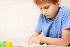 Peinture de garçon avec le pinceau et les peintures colorées de gouache et d'aquarelle Photo stock