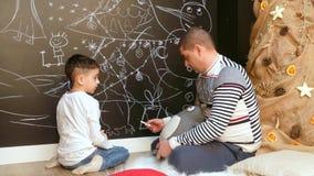 Peinture de garçon et d'homme sur l'arbre de Noël de mur banque de vidéos