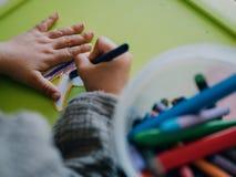 Peinture an de la fille trois avec des couleurs sur la table verte photo stock